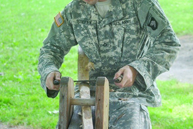 Private 1st Class Peter Steffy, 1st Battalion, 502nd Infantry Regiment, 2nd Brigade Combat Team, 101st Airborne Division, uses a saw horse to craft his own bow from a red elm tree under the direction of Frank Otero.