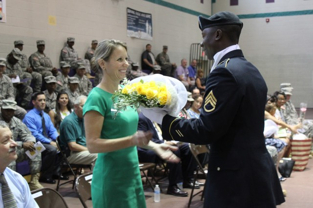 Flowers are presented to the spouse of 597th Trans. Bde. commander