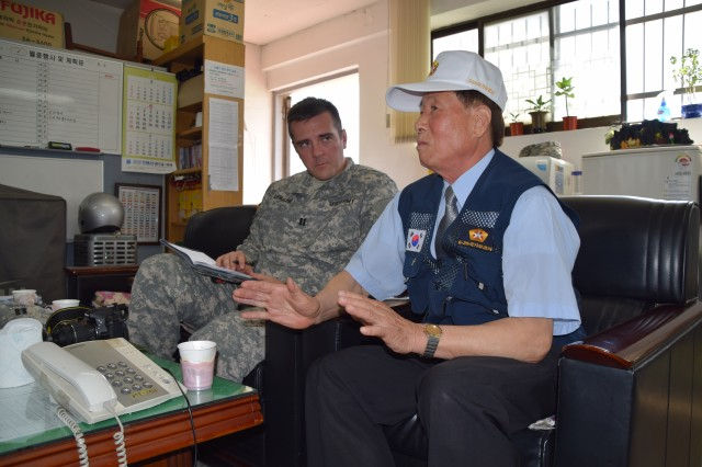 Hoe Su Lee, a Korean War veteran, speaks with Capt. William Leasure, 35th Air Defense Artillery Brigade public affairs officer, at the Ministry of Patriots and Veterans Affairs -- Osan branch June 3, 2015 about serving during the Korean War. Lee served in the military for eight years. (Photo by Staff Sgt. Heather A. Denby, 35th ADA Public Affairs)