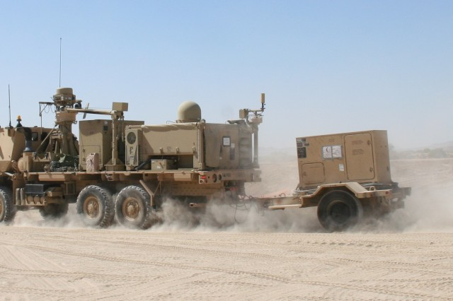 """A Warfighter Information Network Tactical Increment 2 Tactical Communications Node joins the convoy heading out into the training """"box"""" at the National Training Center, Fort Irwin, Calif., on May 28, 2015. The TCN operates on the move and at the halt, and helps provide the network to the brigade and battalion command post. (U.S. Army photo by Amy Walker, PEO C3T)"""