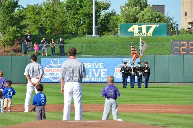 Two of the Springfield Cardinals players join local recreation league baseball players in honoring the American Flag prior to the Springfield Cardinals Military Appreciation game Saturday. The Maneuver Support Center of Excellence Color Guard joined various Soldiers, Sailiors and Airmen from Fort Leonard Wood to participate in the pre-game ceremonies.