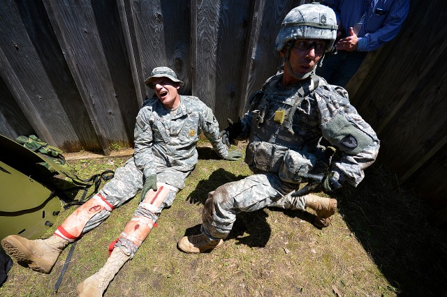 Sgt. 1st Class Benjamin Bryan, 404th Army Field Support Brigade, Schofield Barracks, Hawaii, tends to a casualty during a situational training exercise as part of ASC's Best Warrior Competition at Rock Island Arsenal, Illinois, June 23. (Photo by Justin Graff, ASC Public Affairs)