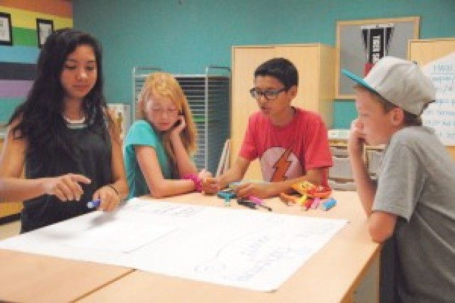 From left, Briana Rables 14; Haley Larosa, 12; Miguel Sosa, 12; and Hunter Larosa, 12, collaborate on a poster to market their baby-sitting services during a Child, Youth and School (CYS) Services baby-sitting workshop.
