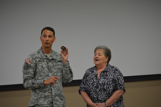 Gloria Aubuchon, budget analyst for the Armed Scout Helicopter Project Office, gets a surprise recognition from Brig. Gen. Bob Marion, program executive officer for aviation, during the ASH change of responsibility ceremony June 18. Aubuchon received the PEO coin and was lauded for her efforts in properly managing and executing funds, ensuring there were no gaps, especially during a period of significant personnel losses in the office.