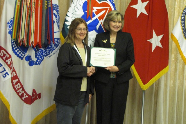 Mary Birdsong recieves a Commander's Award for Civilian Service from outgoing AMCOM deputy commander Cathy Dickens.