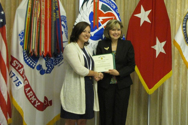 Julie Frederick recieves a Commander's Award for Civilian Service from outgoing AMCOM deputy commander Cathy Dickens.