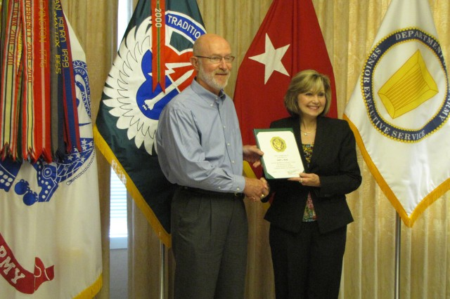 Gary Reas recieves a length of service award from outgoing AMCOM deputy commander Cathy Dickens.