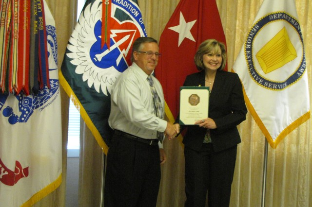 """William """"Bruce"""" Cline receives a length of service award from outgoing AMCOM deputy commander Cathy Dickens."""
