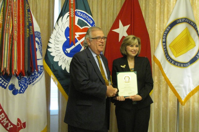 Fred Allen recieves a length of service award from outgoing AMCOM deputy commander Cathy Dickens.