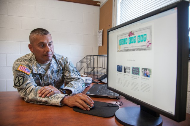 Master Sgt. George Isla looks through Family photos posted on his wife's blog site.