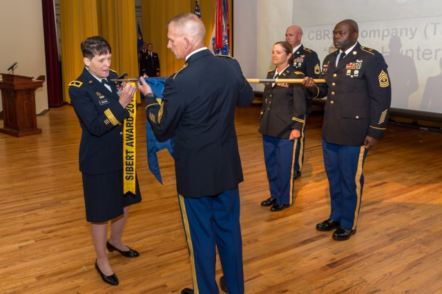 The 28th Chief of Chemical, Brig. Gen. Maria Gervais, adds a Sibert Award streamer to a unit guidon.