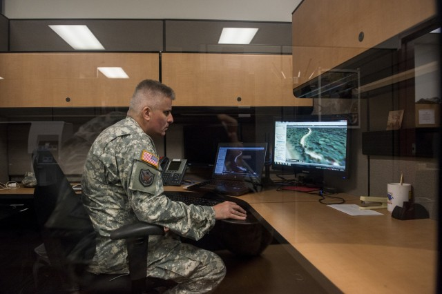 Master Sgt. Steven Lotz, geospatial analyst for the 416th Theater Engineer Command, navigates digitally through a map created using a geographic information system software of a local area in Darien, Ill., June 30, 2015.