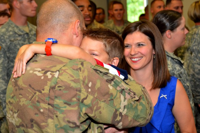 Staff Sgt. Scott Penney, detail noncommissioned officer in charge, is greeted from deployment by his wife April and their son, Kyndon, during a welcome-home ceremony July 1 at the 92nd Military Police Battalion headquarters.