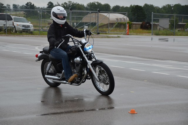 While wearing all of the prescribed personal protective equipment, such as over-the-ankle boots, long sleeves and pants, gloves and a helmet, a service member completes a cornering maneuver during a Motorcyle Basic Rider Course July 1.