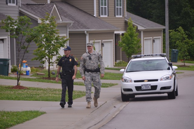 From left, Robert Ishmael, Fort Leonard Wood police officer, and Sgt. Anthony Narug conduct a foot patrol of the Woodlands neighborhood.