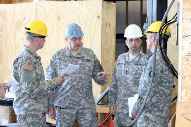 Senior Instructor John Goodlaxson provides students guidance in the Interior Electrician Course at Fort Dix, N.J., June 7, 2015. During the course, students learn the basics of installing electrical wires and devices, as well as working with circuitry of all types commonly found in homes and businesses.