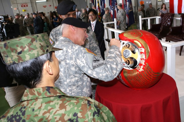 Maj. Gen. James C. Boozer, Sr., outgoing U.S. Army Japan and I Corps (Forward) commander, fills in the eye of his Daruma doll during the change of command ceremony held July 8 at Kastner Army Airfield Hanger. The Daruma doll is one of the most popular talismans of good luck in modern Japan, and it is received upon command and only one eye is filled in. After successfully completing command, Boozer fills in the other eye to represent a completed mission.