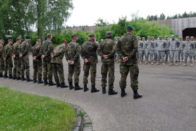 Soldiers from the Bundeswher (German Armed Forces) and 3-158th Assault Helicopter Battalion, 12th Combat Aviation Brigade stand in formation in anticipation for their marksmanship awards, June 10, 2015, at the Roth, Germany shooting range, as part of the German and U.S. Armies' marksmanship assessment.