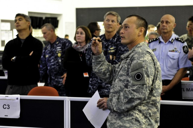 Maj. Siegfried Ramil, a battle major with I Corps, briefs Vice Adm. Robert Thomas, 7th Fleet commander, about the current operations I Corps is tracking for their command portion of Exercise Talisman Sabre 15 during a tour with other non-governmental agencies for an interagency observers day visit at Gallipoli Barracks, Australia, July 14, 2015.
