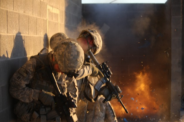 Soldiers, from the 1st Armored Division, react to an explosion while participating in an urban combat exercise on a Fort Bliss, Texas, training facility, May 11-12, 2011.