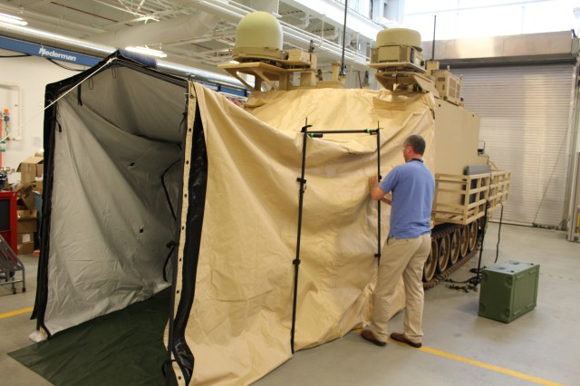 """Brad McNeilly-Anta, product lead, CERDEC CP&I, erects the tent to the Combined Arms Battalion, or CAB, Mobile TAC, which allows commanders in heavier units to """"command from the hatch."""" (U.S. Army CERDEC photo by J. Tyler Barton)"""