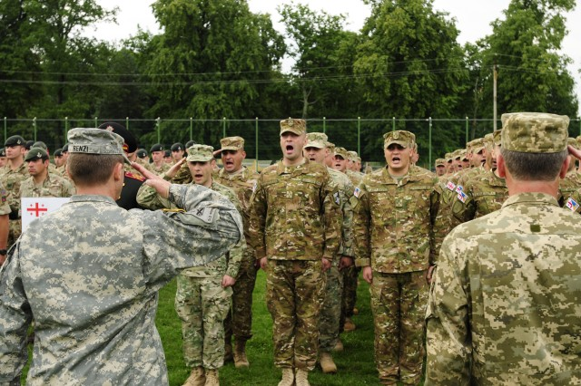 "Col. Alfred Rienzi, chief of assessments, U.S. Army Europe G3 for operations, gives his remarks to the ""Warriors"" of the multi-national Exercise Rapid Trident 2015 during the opening ceremony held at the International Peacekeeping and Security Center near Yavoriv, Ukraine, July 20, 2015."