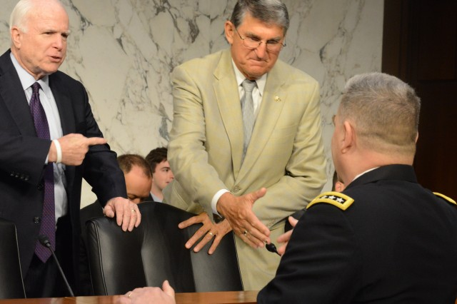 Gen. Mark A. Milley is greeted by Sen. Joe Manchin III (D-WV) with Sen. John McCain (R-AZ) looking on before a Senate Armed Services Committee hearing regarding Milley's nomination to become the next Army chief of staff, July 21, 2015.