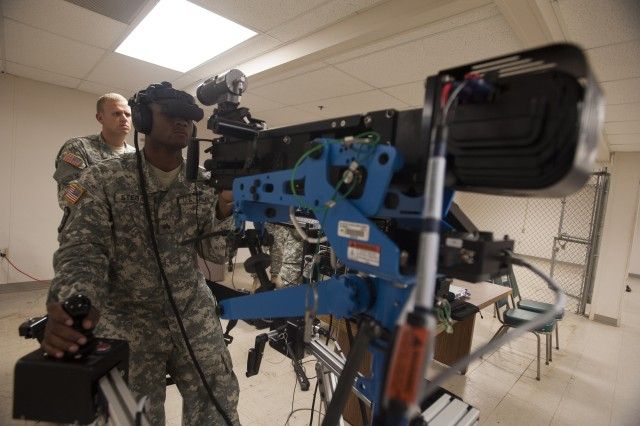 Sergeant Jarrod Stegall, a vehicle crewmember with the 626th Brigade Support Battalion, 3rd Brigade Combat Team, 101st Airborne Division, scans for targets during a simulated convoy here July 16, 2015. Stegall conducted training on the 3rd Brigade Combat Team's unstabilized gunnery trainer-individual, the first of its kind in the active component Army, which allows unit master gunners to build scenarios for crew gunners to virtually engage targets and validate them before conducting live-fire gunnery tables. The system, which consists of a simulated weapon system, a heads up display visor and a headset that allows the gunner to communicate with a synthetic vehicle commander and driver, replaces the Reconfigurable Vehicle Tactical Trainer, a full-scale mockup of a vehicle that is designed to focus more on crew drills and convoy scenarios. In addition to the training the system offers, the UGT-I allows for the unit master gunners, senior gunners and leadership to receive immediate results from a training simulation and identify areas where a trainee may need additional training time before becoming certified to conduct live-fire table gunnery. (U.S. Army photo by Staff Sgt. Joel Salgado, 3rd Brigade Combat Team Public Affairs)