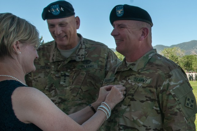 """FORT CARSON, Colo. -- Becky Daugherty pins the rank of brigadier general to her husband, the 4th Infantry Division and Fort Carson Deputy Commanding General Brig. Gen. Timothy J. Daugherty, during a promotion ceremony led by Chief of Staff of the Army Gen. Raymond T. Odierno on Founders Field, July 23, 2015. """"We need leaders who can lead them,"""" said Odierno during the ceremony. """"We need leaders who are dynamic. We need leaders who understand how to be adaptive, innovative and capable of doing the important things that are necessary for us to be successful. We need leaders who are competent, committed and have incredible character. All of these define Tim Daugherty."""""""