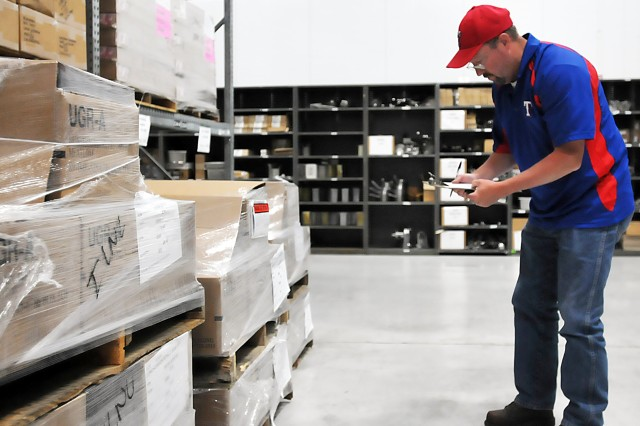 An employee inventories items in a building operated by LRC-McCoy in Wisconsin, that stocks kitchen utensils, linen, and bagged ice among other supplies, July 9. (Photo by Jon Micheal Connor, ASC Public Affairs)