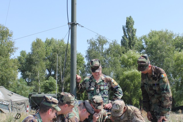 U.S. Army Sgt. Chreston Anderson, kneeling right, a paratrooper assigned to the 173rd Airborne Brigade, conducts training on FM radios with, from left, Moldovan Army Capt. Ion Cebotari, Capt. Victor Goja, Capt. Valentin Mardari, 1st Lt. Victor Turculet, Pvt. Vadin Modirea and Pvt. Jvan Jintea, from the Moldovan army Signal Battalion as part of Exercise Common Effort in Balti Training Area, Moldova, July 20, 2015.