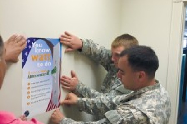 "Staff Sgt. Alfonso Calderon (front), 2nd Stryker Brigade Combat Team, 25th Infantry Division, and Pvt. Kode Love, 3rd BCT, 25th ID, place a ""Five Ways of Saving the Army Money"" poster at the Army Single Soldier Housing Facility, Schofield Barracks."