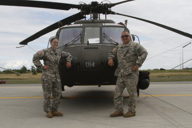New York Army National Guard Warrant Officer Meghan Polis, left, and Chief Warrant Officer 3 Stephen Polis - a daughter and father, who are both assigned to Company B 3rd Battalion 142nd Assault Helicopter Battalion, pose in front of a UH-60 Black Hawk helicopter on Fort Drum, N.Y., July 22, 2015.