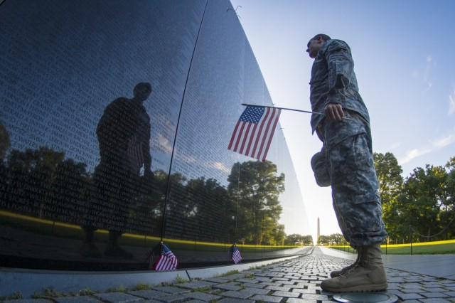 "A U.S. Army Reserve Soldier reads some of the 58,272 names etched into ""The Wall"" of the Vietnam Veterans Memorial in Washington, D.C., as the sun rises, July 22, 2015."