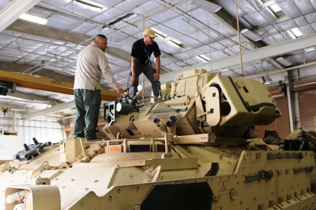 Two Capability Package Directorate's integration team members work on a Stryker, which is being outfitted with equipment for Network Integration Evaluation 16.1/Army Warfighter Assessment on Fort Bliss, Texas.