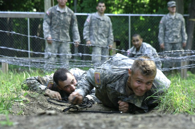 Troopers assigned to A Troop, 1st Squadron, 89th Cavalry Regiment, 2nd Brigade Combat Team, 10th Mountain Division (LI), low crawl under a barbed wire obstacle at the combined obstacle course medical evacuation lane during the McChrystal-Briles Competition on Fort Drum.