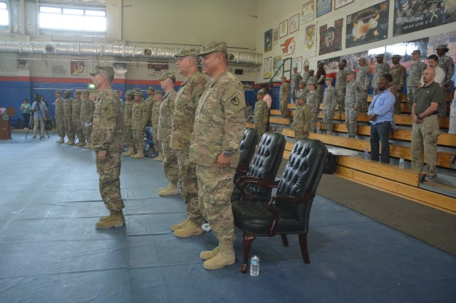 Col. Christopher L. Day (left), 401st Army Field Support Brigade commanding officer, stands in front of the official party at the conclusion of the change of command ceremony at Camp Arifjan, Kuwait July 16, in which he assumed command from Col. Matthew J. Ferguson (foreground).
