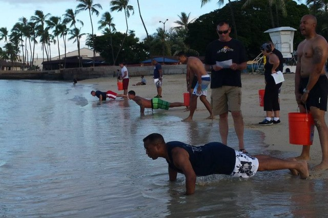 Soldiers of the HHC, 311th Signal Command do pushups at the waters edge of Hickam Beach during Organizational Week's 'Commander's Cup' on July 15, 2015. Phyiscal excercises included: planks, pushups, situps, lunges, sprints, and swimming.