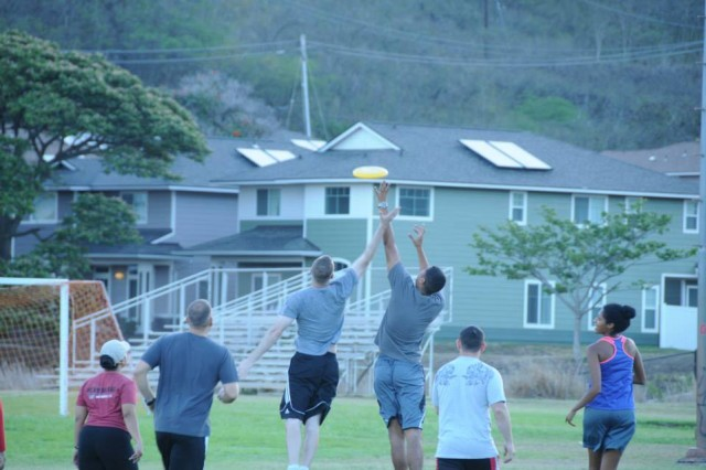 Two Soldiers from HHC, 311th Signal Command, reach for the Frisbee during the Ultimate Frisbee game at the Aliamanu Military Reserve fields. The Soldiers of HHC, 311th Signal Command went head-to-head, practicing teamwork and implementing a bit of friendly competition on July 14, 2015.