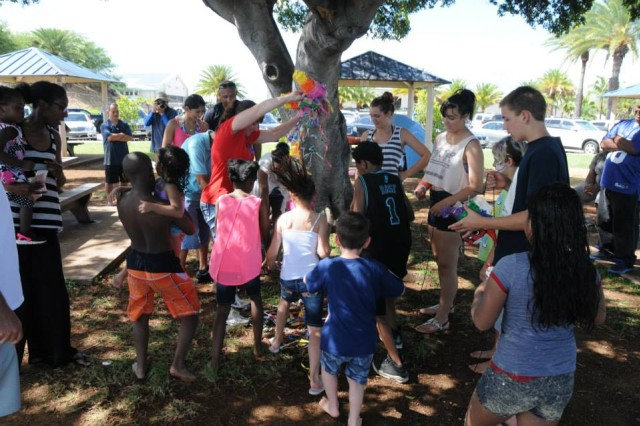 Children of the Soldiers and civilians from 311th Signal Command, rush to grab as much candy as they can from a piñata that has recently split open. Soldiers, Civilians, Families and friends all enjoyed the beach day at Hickam Beach, which marked the end of Organizational Week on July 17, 2015.