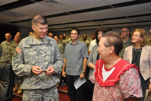 Maj. Gen. Todd McCaffrey, United States Army Pacific Chief of Staff, presents the Commander's Coin of Excellence to Ms. Loo in front of fellow Soldiers and Civilians, as a token of appreciation for her 54 years of Federal service, on Ft. Shafter, HI, Nov. 25, 2014.