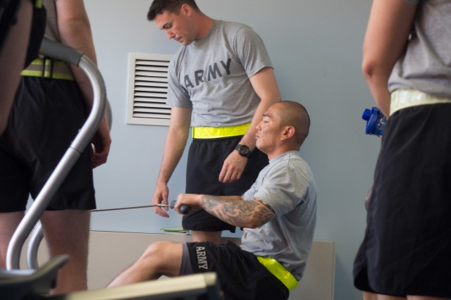 "Class leader, Staff Sgt Toby Maratita (sitting) and Staff Sgt. William Stanley demonstrate proper operation of ""The Rower"" to their classmates at Natcher Physical Fitness Center during Master Fitness Trainers course, Fort Knox, Ky. Jun 17, 2015."