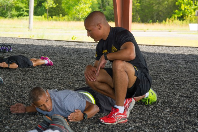 Instructor Staff Sgt. Nicholas Rice supervises a student during strength exercise session at Physical Training Pit, during Master Fitness Trainers course, Fort Knox, Ky. Jun 17, 2015.