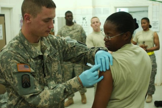 Spc. Joshua Ryan, a medic with the 16th Special Troops Battalion, 16th Sustainment Brigade, administers the influenza vaccine to Staff Sgt. Jacqueline Atkins at the troop medical clinic at Contingency Operating Base Q-West, Iraq.