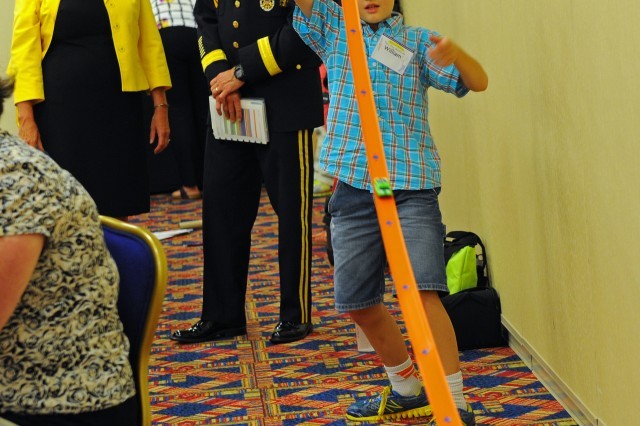 Army Vice Chief of Staff Gen. Daniel Allyn and his wife, Debbie, watch a youngster run through one of the Hot Wheels 'speedometry' experiments at the 17th National Training Seminar hosted by the Military Child Education Coalition in Washington, D.C., July 27-28, 2015.