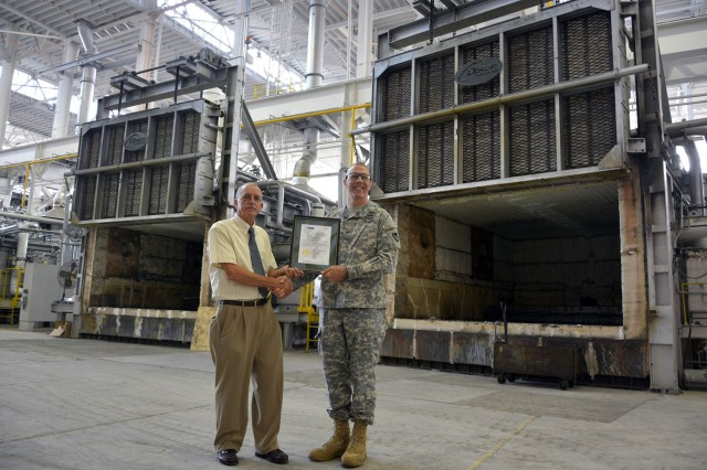 Tracy Rudolph, the president and chief operating officer of Electralloy, and Arsenal Commander Col. Lee H. Schiller Jr. standing in front of the three Electralloy furnaces while holding the new American Bureau of Shipping certificate.