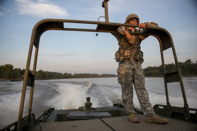 Pfc. Husni Ayesh, from Greenville, N.C., a bridge crew member for the 310th Engineer Company (Multi-Role Bridge), out of Fort A.P. Hill, rides on an MK2 bridge erection boat in the early morning of Operation River Assault 2015, a bridging training exercise involving Army Engineers and other support elements to create a modular floating bridge on the water across the Arkansas River at Fort Chaffee, Ark., Aug. 4, using improved ribbon bridge bays. The entire training exercise lasted from July 28 to Aug. 4, 2015, involving one brigade headquarters, two battalions and 17 other units, to include bridging, sapper, mobility, construction and aviation companies. (U.S. Army photo by Master Sgt. Michel Sauret)