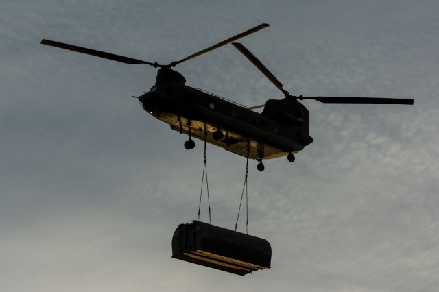 A CH-47 Chinook flown by Bravo Company, 7th Battalion, 158th Aviation Regiment, out of Fort Hood, Texas, carries an improved ribbon bridge bay to the Arkansas River during Operation River Assault 2015, a bridging training exercise involving Army Engineers and other support elements to create a modular floating bridge on the water at Fort Chaffee, Ark., Aug. 4. The entire training exercise lasted from July 28 to Aug. 4, 2015, involving one brigade headquarters, two battalions and 17 other units, to include bridging, sapper, mobility, construction and aviation companies. (U.S. Army photo by Master Sgt. Michel Sauret)