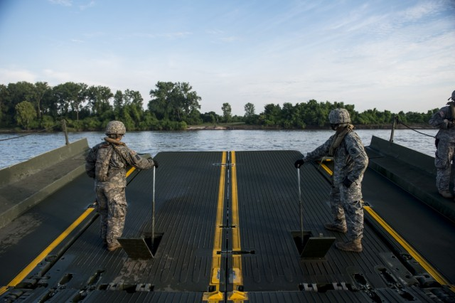 Two Army Reserve Soldiers from the 310th Engineer Company (Multi-Role Bridge), from Fort A.P. Hill, Va., ride on a floating ramp to lower it onto a shore during Operation River Assault 2015, a bridging training exercise involving Army Engineers and other support elements to create a modular floating bridge on the water across the Arkansas River at Fort Chaffee, Ark., Aug. 4, using improved ribbon bridge bays. The entire training exercise lasted from July 28 to Aug. 4, 2015, involving one brigade headquarters, two battalions and 17 other units, to include bridging, sapper, mobility, construction and aviation companies. (U.S. Army photo by Master Sgt. Michel Sauret)