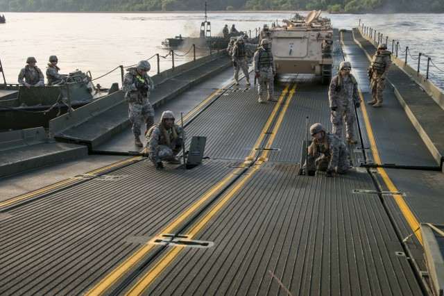 Army Reserve Soldiers transport an armoured personnel carrier on an improved ribbon bridge to a shore along the Arkansas River during Operation River Assault 2015, a bridging training exercise involving Army Engineers and other support elements to create a modular floating bridge at Fort Chaffee, Ark., Aug. 4, using improved ribbon bridge bays. The entire training exercise lasted from July 28 to Aug. 4, 2015, involving one brigade headquarters, two battalions and 17 other units, to include bridging, sapper, mobility, construction and aviation companies. (U.S. Army photo by Master Sgt. Michel Sauret)